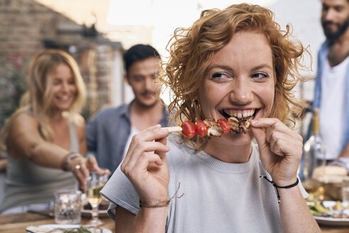Young woman eating meat skewer at a backyard patry with friends - PDF01855