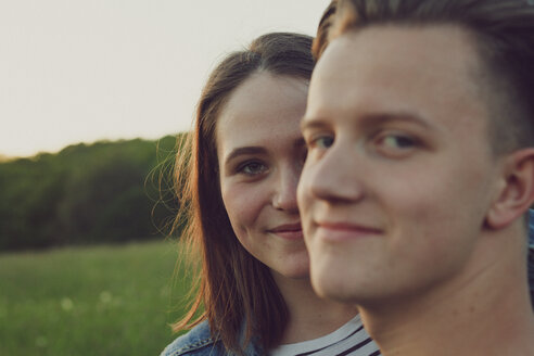 Portrait of happy teenage girl hiding behind her boyfriend - ANHF00094