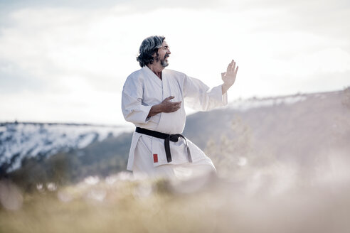 Senior man practicing karate outdoors - OCMF00304