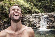 Germany, Upper Bavaria, Bavarian Prealps, lake Walchen, young man is laughing in a torrent - WFF00059