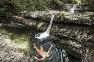 Germany, Upper Bavaria, Bavarian Prealps, lake Walchen, young man is swimming in a plunge pool - WFF00065