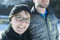 Portrait of smiling woman with man outdoors in winter - MKFF00453