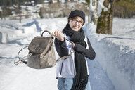 Portrait of smiling woman with backpack on a winter walk - MKFF00468