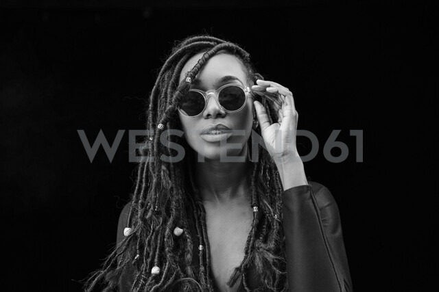 Portrait of woman with dreadlocks wearing sunglasses in front of black background - FMKF05525