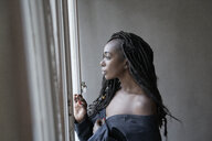 Profile of woman with dreadlocks looking out of window - FMKF05528
