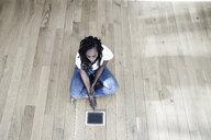 Woman sitting on the floor using digital tablet - FMKF05534