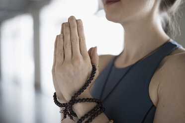 Close up woman with prayer beads practicing yoga meditation with hands at heart center - HEROF30001