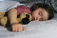 Portrait of toddler girl sleeping in bed  with a soft toy dog - GEMF02910