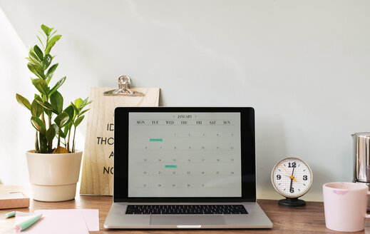 Opened laptop with a calendar on desk at home office - MOMF00633