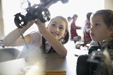 Pre-adolescent boy and girl assembling robotics in classroom - HEROF30061