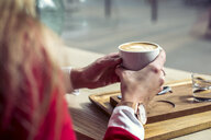 Woman's hands holding cup of coffee, close-up - ACPF00491