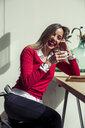 Portrait of laughing woman sitting in a coffee shop drinking cup of coffee - ACPF00494