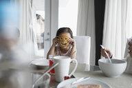 Portrait girl holding pancake smiley face at breakfast table - HEROF30102