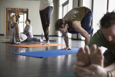 Man practicing yoga crow pose in yoga class studio - HEROF30128
