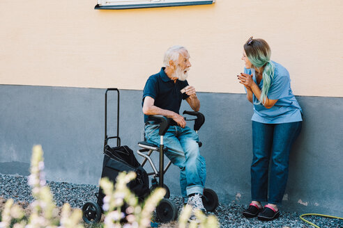Smiling female nurse clapping while looking at senior man sitting on wheelchair against wall at back yard - MASF11525