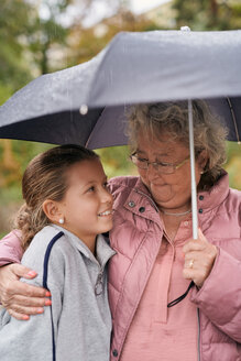 Grandmother embracing granddaughter while sharing umbrella with her in park during rainy season - MASF11543