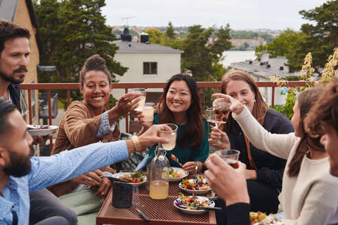 Happy friends toasting drinks while sitting on terrace - MASF11576