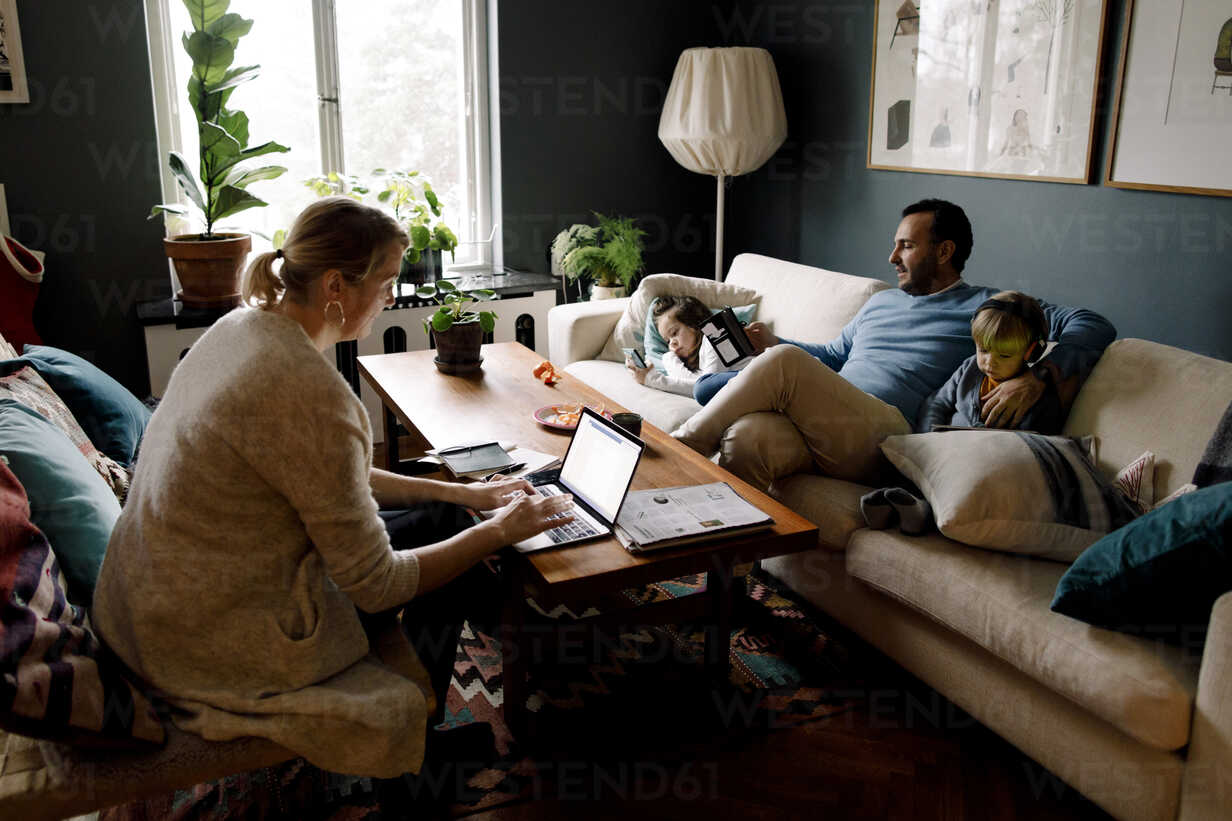 Family using various technologies in living room at home - MASF11588 - Maskot/Westend61