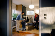 Father helping daughter in getting dressed seen through doorway at home - MASF11591