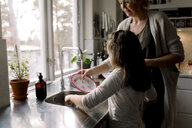 Daughter helping mother in kitchen at home - MASF11600