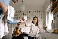 Smiling daughter giving cup to father in kitchen at home - MASF11603