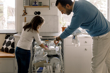Father and daughter arranging utensils in dishwasher at kitchen - MASF11606