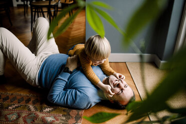 Playful daughter pinching cheerful father's cheeks on floor at home - MASF11612