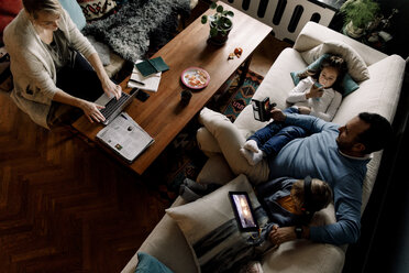 High angle view of family using various technologies in living room at home - MASF11615