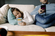 Father and daughter using mobile phones on couch at home - MASF11618