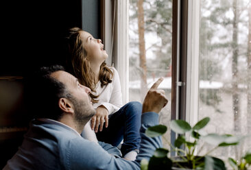 Father and curious daughter looking through window at home - MASF11621