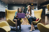 Full length of female multi-ethnic colleagues discussing over laptop and credit card while sitting at airport lobby - MASF11633