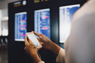 Midsection of businesswoman using phone while standing at airport - MASF11639