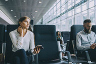 Thoughtful young businesswoman looking away while sitting by colleague at waiting area in airport - MASF11663