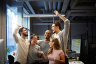 Male and female entrepreneurs cheering in creative office - MASF11705