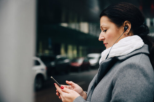Side view of businesswoman listening music using mobile phone while standing on road in city - MASF11747