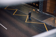 High angle view of businessman using mobile phone while walking on city street - MASF11753