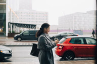 Side view of businesswoman using smart phone while walking on sidewalk against sky in city - MASF11762