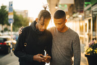 Teenage boy using mobile phone while standing by friend on street in city during sunset - MASF11768