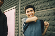 Cheerful young man standing by friend on street in city - MASF11777