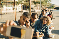 Male friends taking selfie while eating take out food on street in city - MASF11795