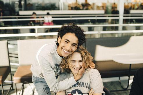 Portrait of cheerful teenage boy embracing friend in restaurant - MASF11819