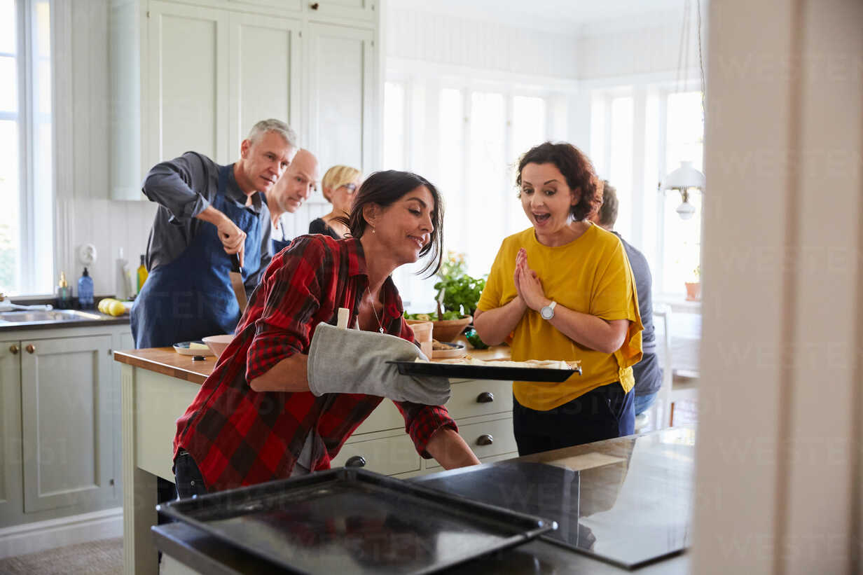 Excited Woman Looking At Friend Baking In Kitchen At Home Stockphoto