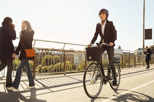 Mature woman riding electric bicycle by commuters on bridge in city against sky - MASF11864