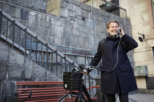 Smiling man talking on smart phone by electric bicycle against building - MASF11879