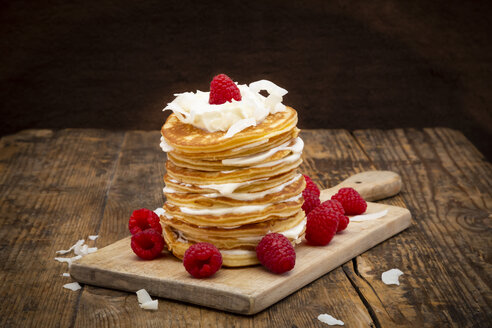 Pancakes made of almond flour with raspberries, greek yogurt and coconut flakes on wooden board - LVF07892