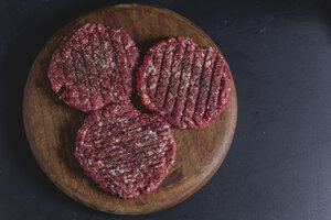 Spiced burger patties on chopping board, from above - STBF00261