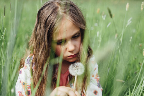 Portrait of unhappy girl looking at  blowball on a meadow - ANHF00100