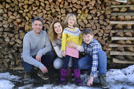 Portrait of happy family in front of stack of wood in winter - ECPF00598
