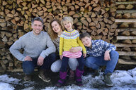Portrait of happy family in front of stack of wood in winter - ECPF00601
