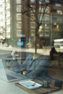 Mature businesswoman with glass of tea laptop in a cafe - JPF00359